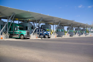 Semi trucks pay at tollbooth at Canadian border